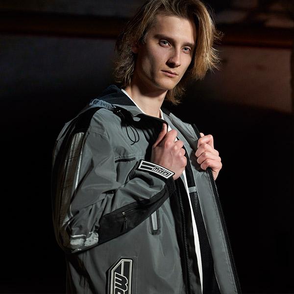 upw-modello-indossa-kway-grigio-in-tessuto-reflective-con-cappuccio