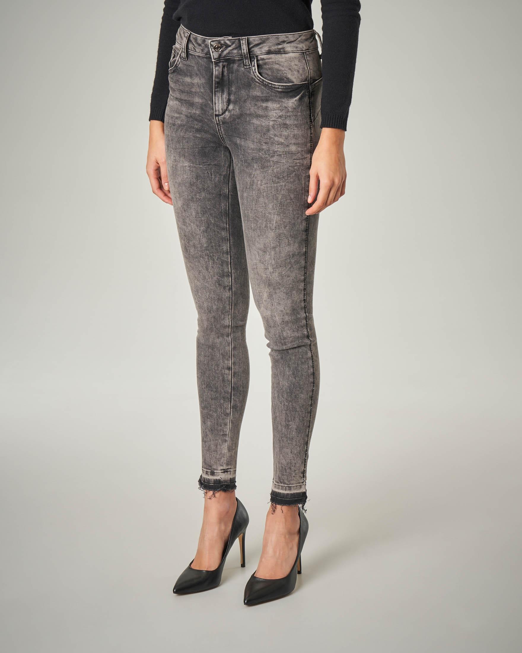 Jeans skinny grigio con orli sfrangiati e strass