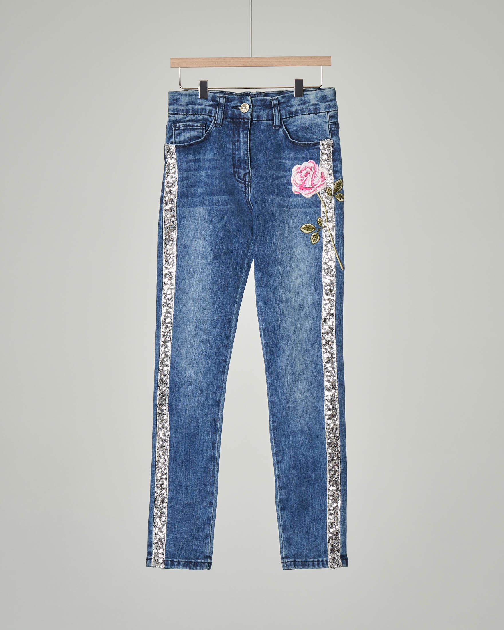 Jeans con bande in paillettes e rosa ricamata