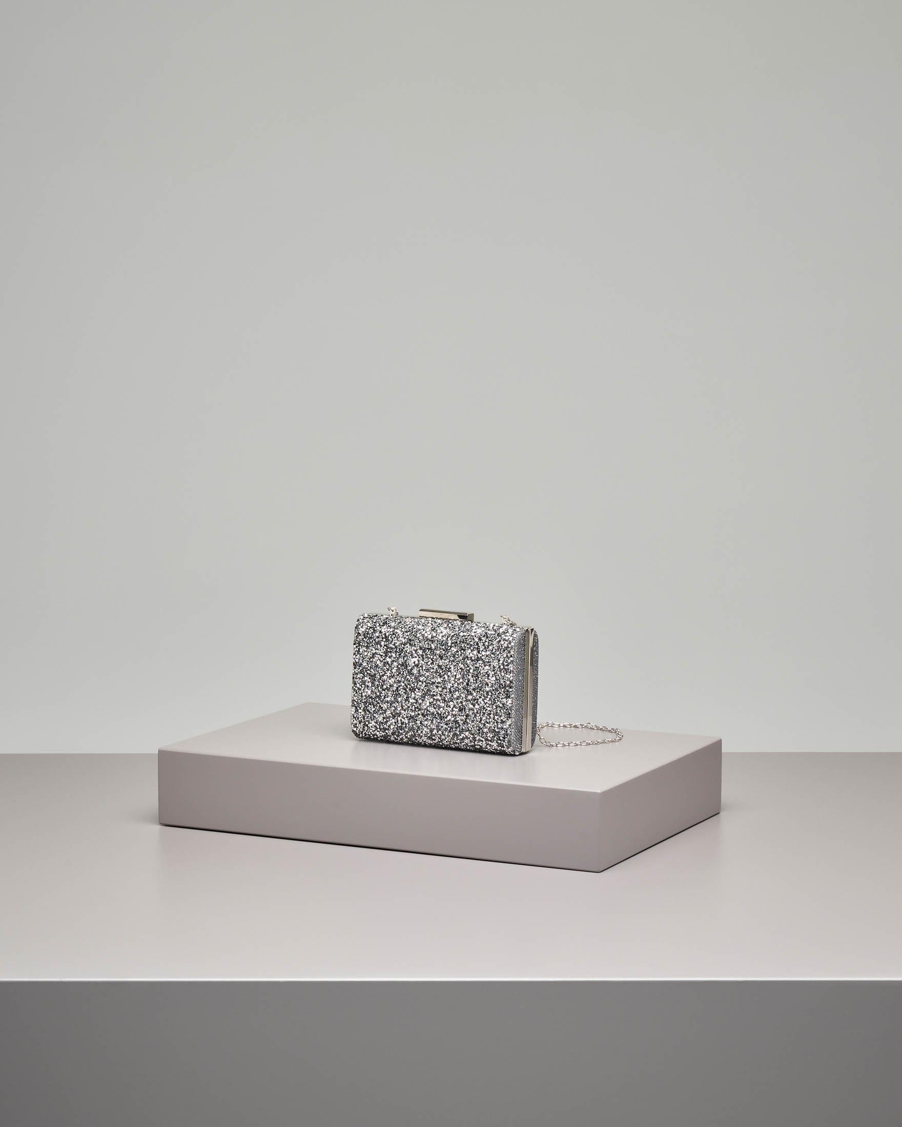 Pochette rigida color argento con chiusura effetto glitter e strass applicati tono su tono