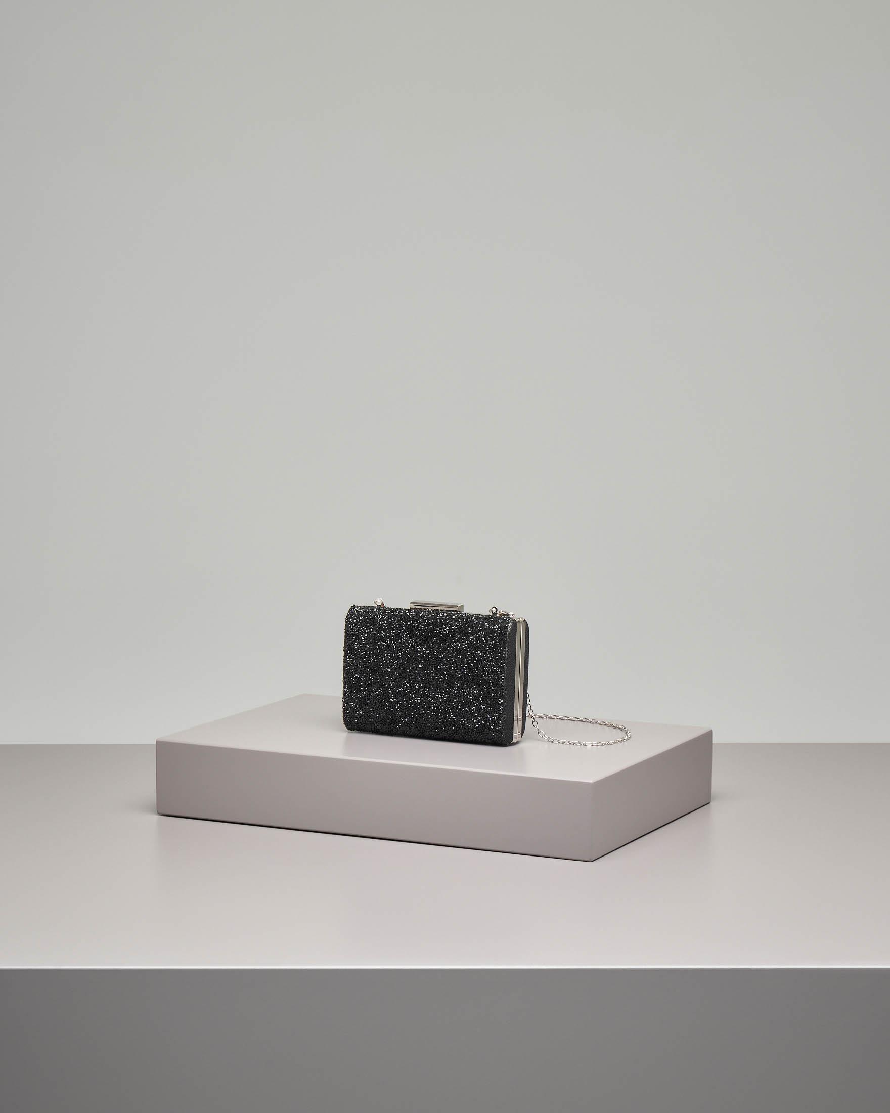 Pochette rigida nera con chiusura effetto glitter e strass applicati tono su tono