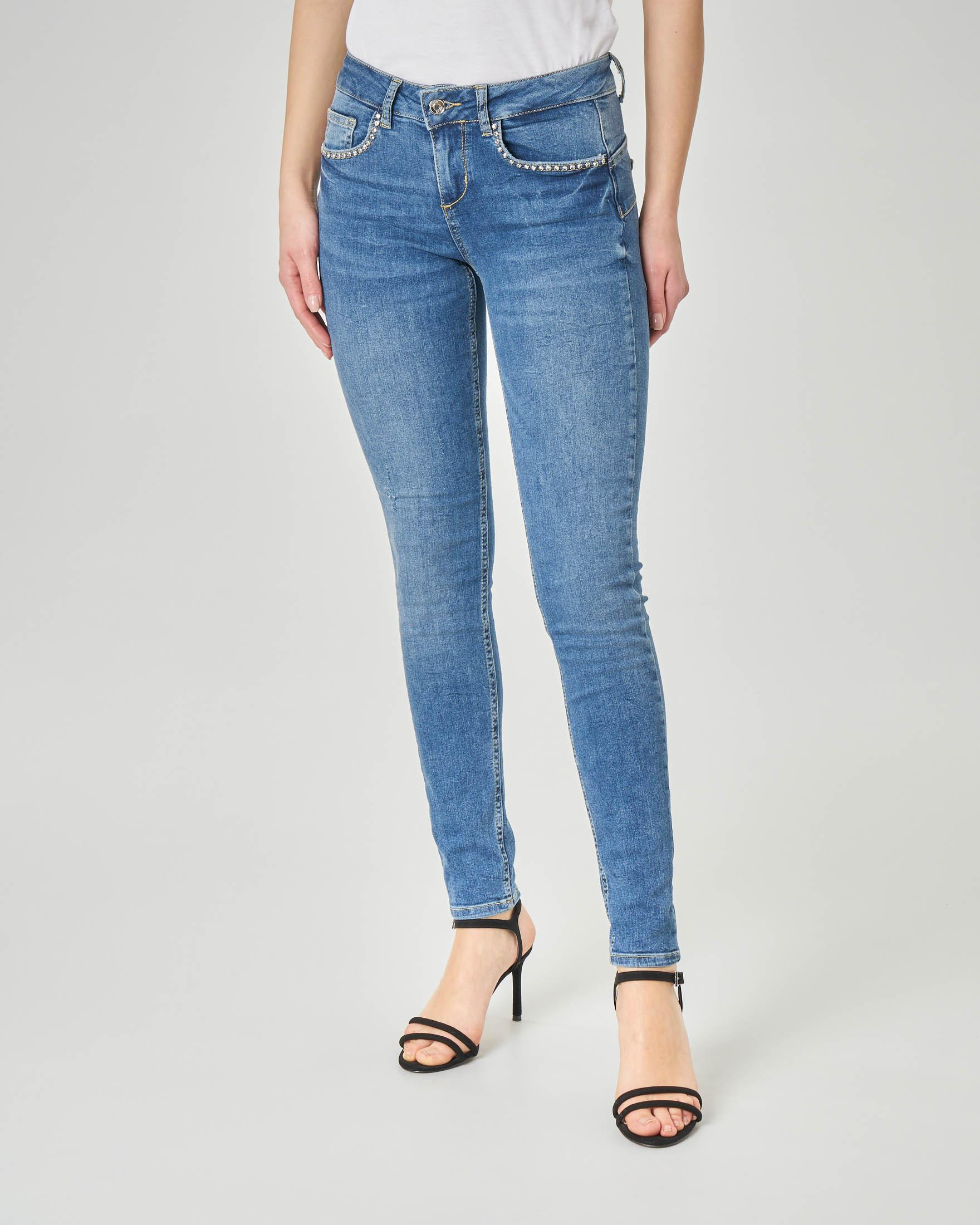 Jeans skinny blu stone washed con strass sulle tasche