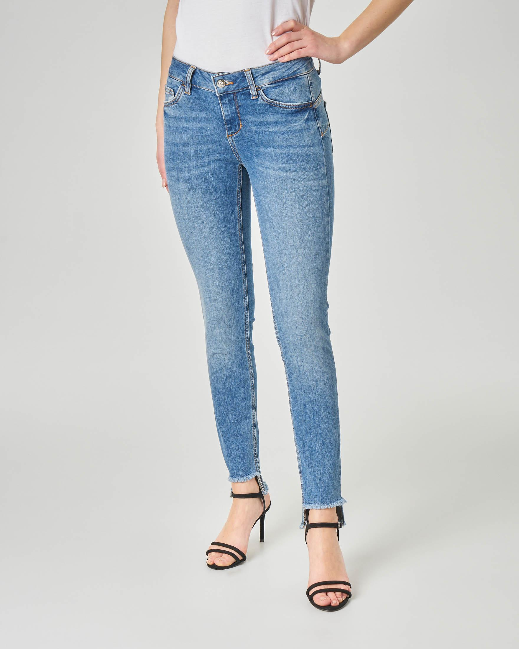 Jeans skinny blu délavé con orli asimmetrici sfrangiati