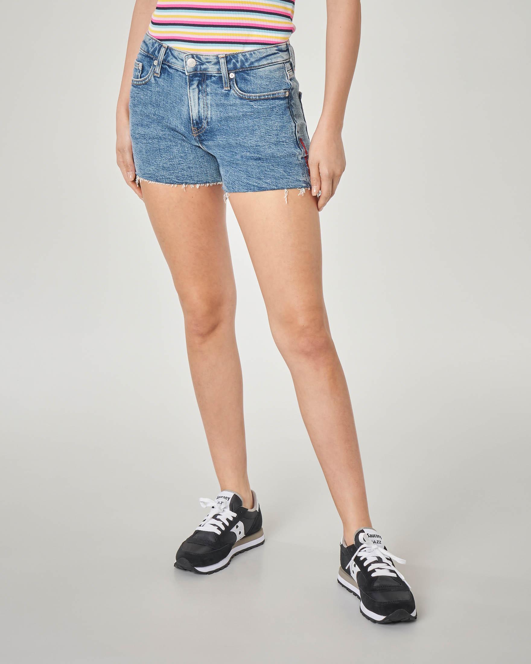 Shorts in denim blu delavè con scritta logo rossa ricamata sulla gamba