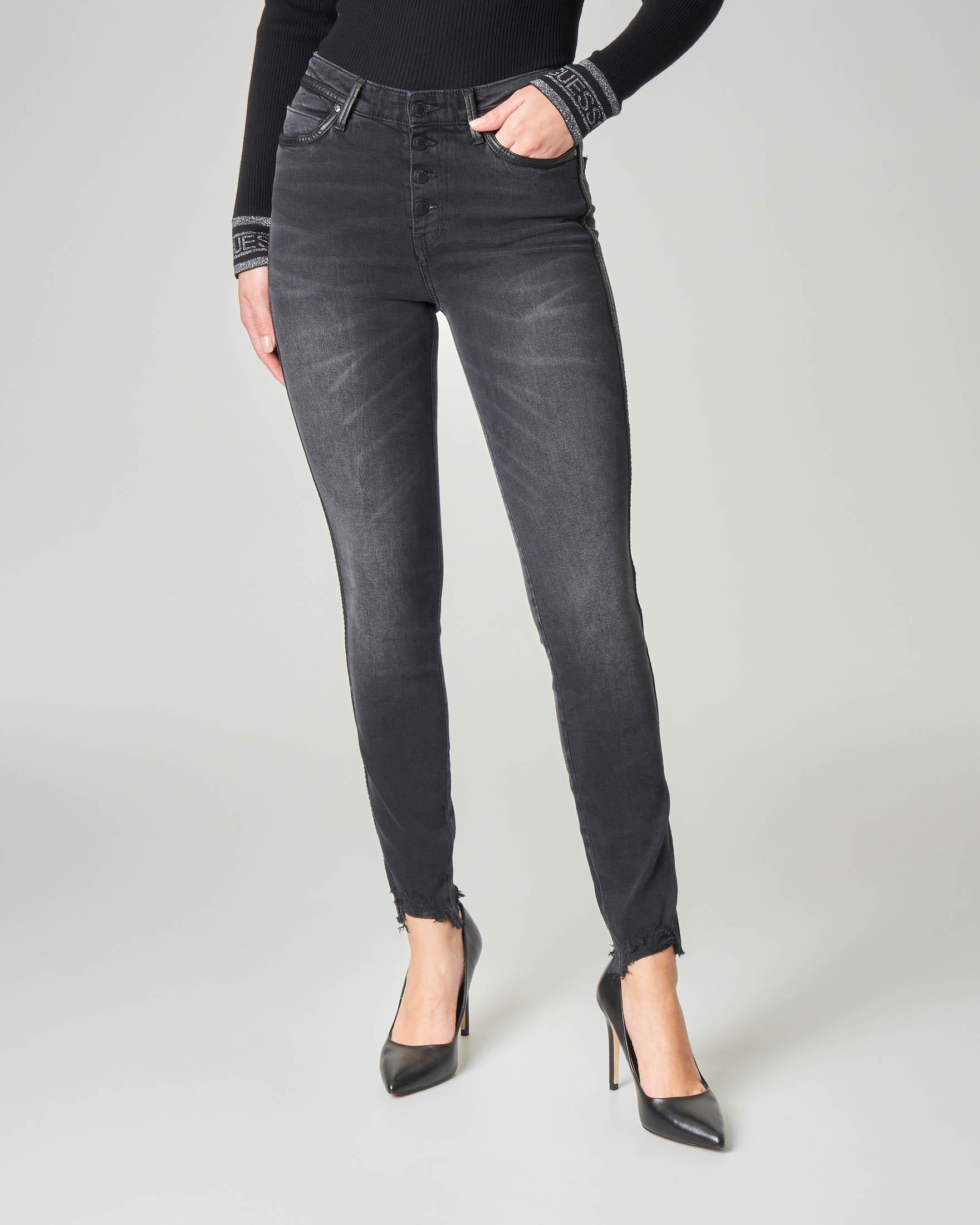 Jeans skinny neri effetto delavè con profili in ecopelle e fondo sfrangiato