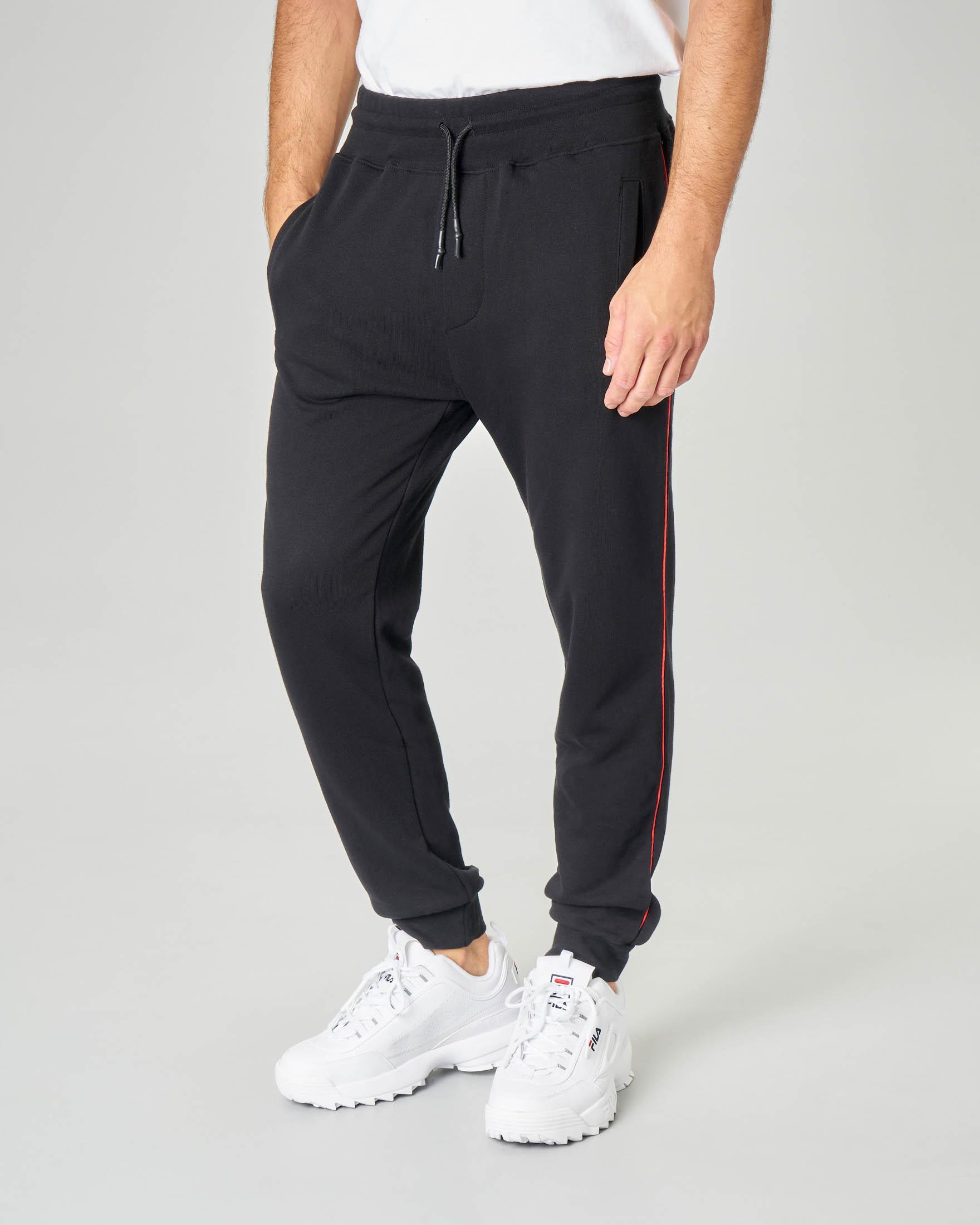 Pantalone nero in felpa con banda rossa fine e logo stampato sul polpaccio