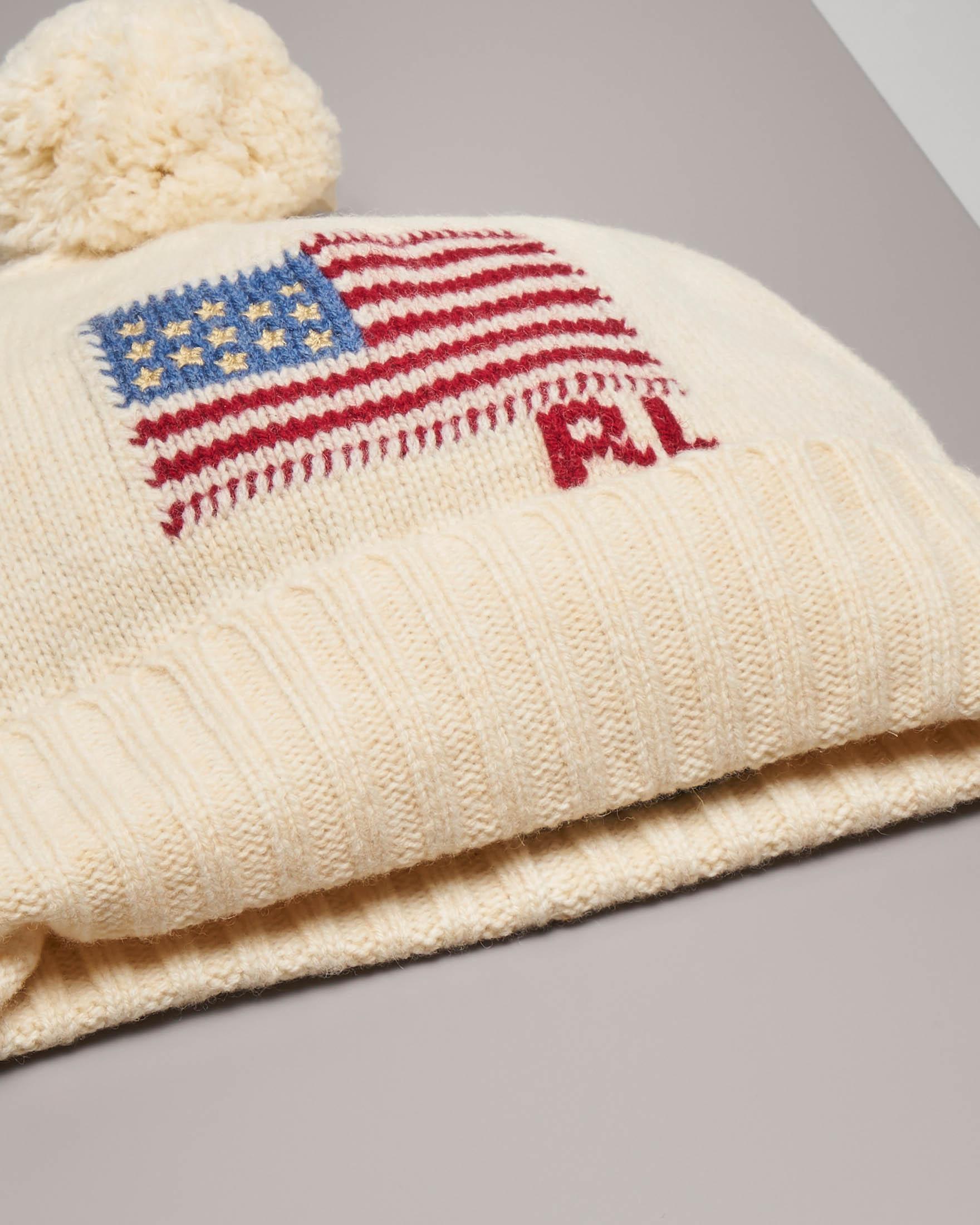 Berretto color avorio con bandiera jacquard e pon pon tono su tono