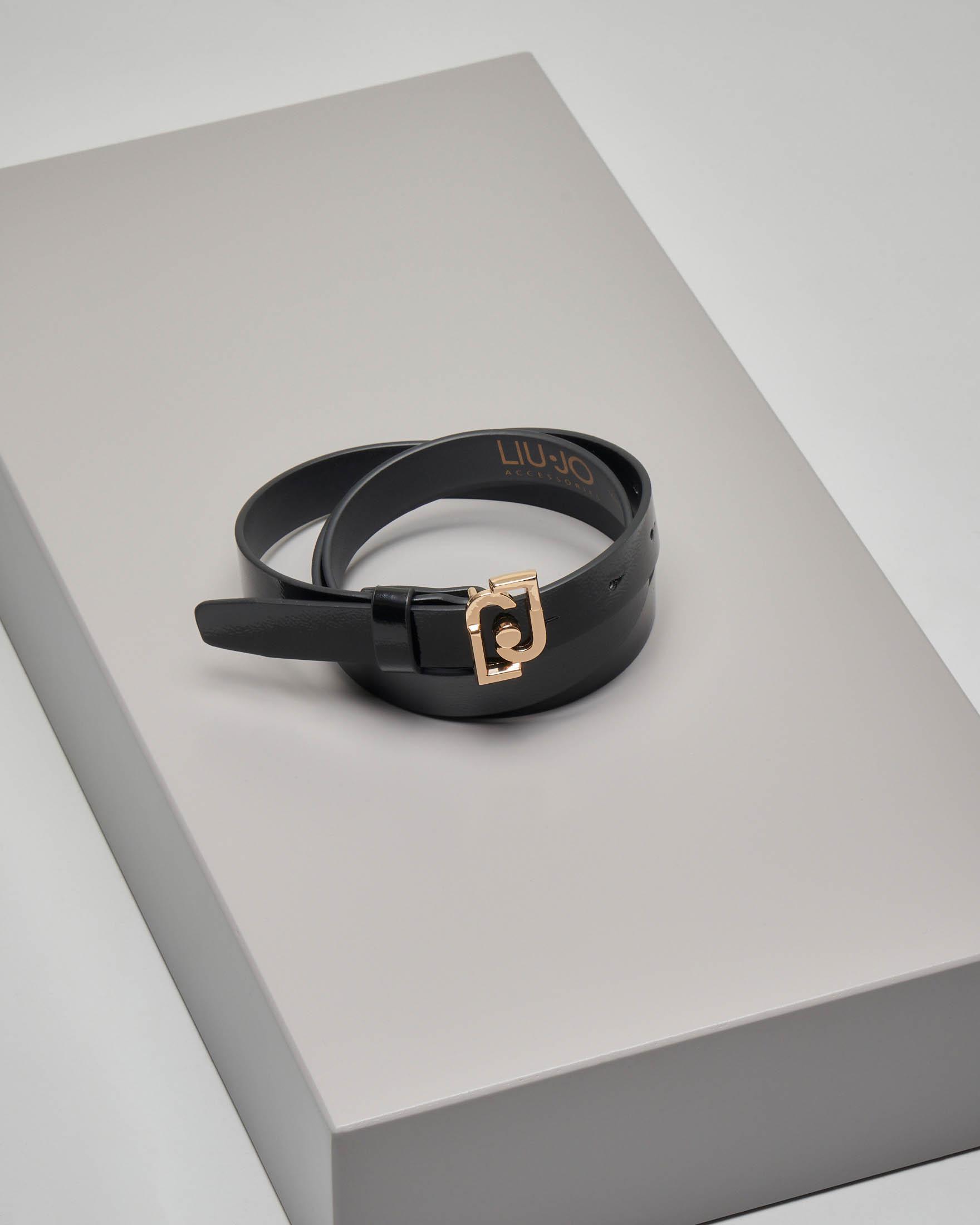 Cintura nera in ecopelle sottile con fibbia con scritta logo dorata