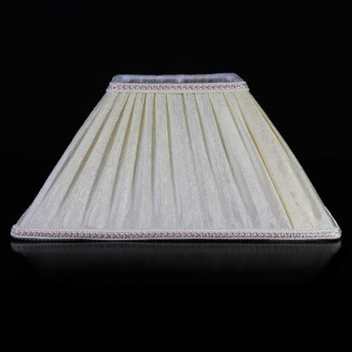 Paralume tronco cono a base quadrata con tessuto avorio stropicciato e passamaneria avorio. Montatura bianca attacco E27.