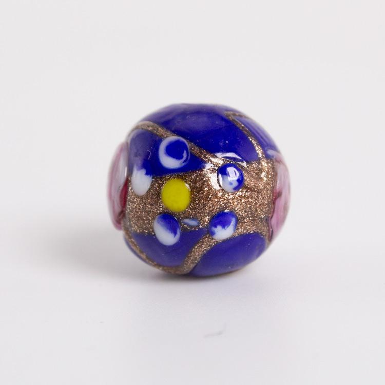 Perla di Murano tonda Ø16. Fiorata con applicazioni a caldo in avventurina e paste policrome. Base vetro blu.