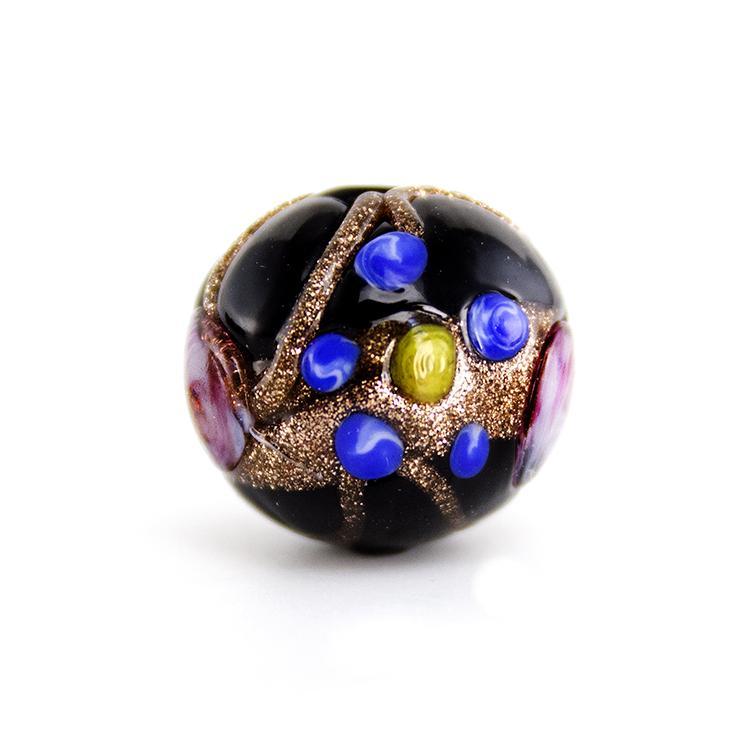 Perla di Murano tonda Ø16. Fiorata con applicazioni a caldo in avventurina e paste policrome. Base vetro nero.