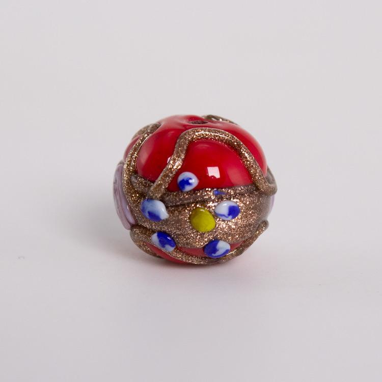 Perla di Murano tonda Ø16. Fiorata con applicazioni a caldo in avventurina e paste policrome. Base vetro rosso.