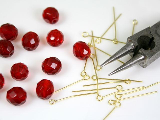 Catena 100 cm perle Ø 10 mm sfaccettate cristallo rosso, spillo a occhiello ottonato brillante.