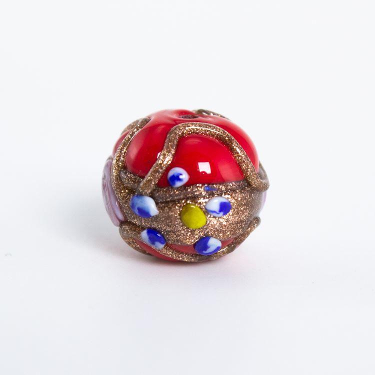 Perla di Murano tonda Ø16. Fiorata con applicazioni a caldo in avventurina e paste policrome. Base vetro rosso, nero, blu cobalto.