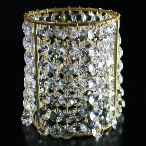 Portacandela base oro allestito con catene di ottagoni in vetro molato 32 facce, colore cristallo, clip oro. Ø 10 cm x H 12 cm.